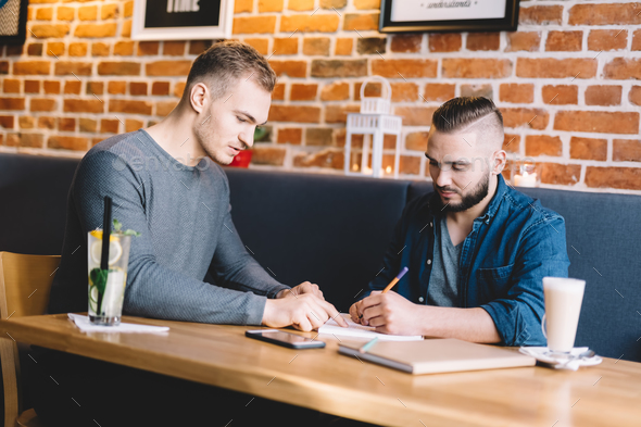 Two young men sitting in a cafe, discussing. - Stock Photo - Images
