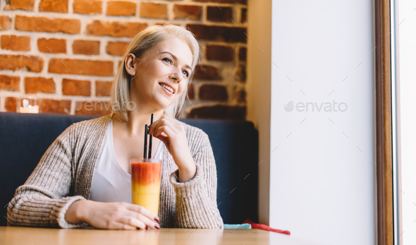 Woman with fancy cocktail looking through the window. - Stock Photo - Images