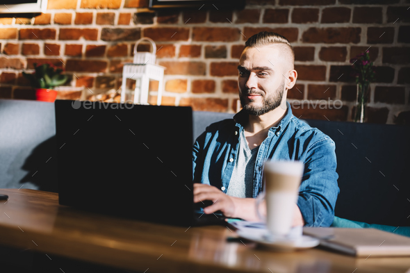 Man typing on a laptop in a cafe. - Stock Photo - Images
