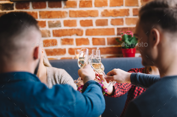 Four people raising glasses to toast. - Stock Photo - Images