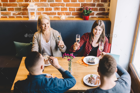 Four people sitting at the table, toasting. - Stock Photo - Images
