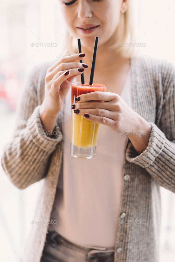 Blonde woman holding a colorful drink - Stock Photo - Images