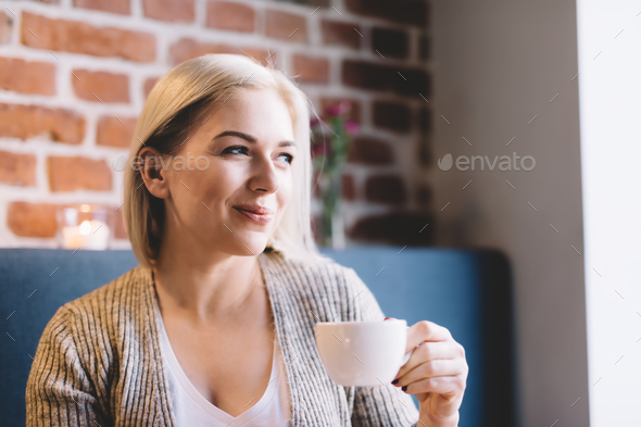 Young woman holding a cup of coffee. - Stock Photo - Images