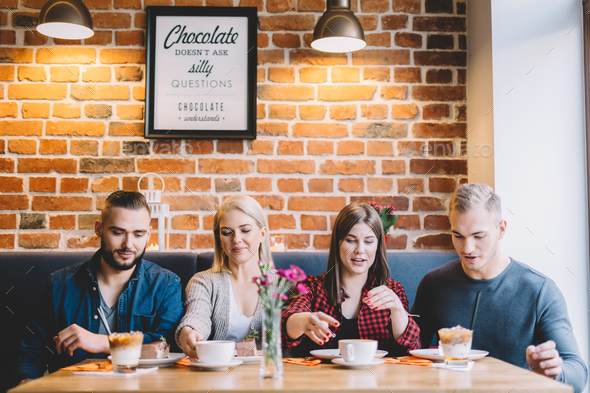 Four people sitting at the table in a cafe - Stock Photo - Images