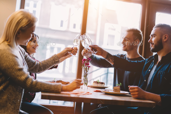 Friends toasting in a restaurant, celebrating. - Stock Photo - Images