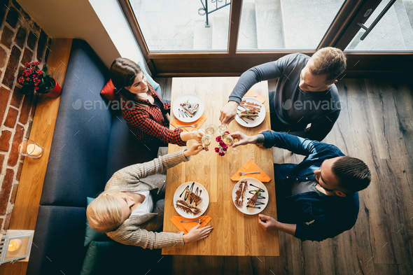 Four friends toasting in a restaurant. Top view. - Stock Photo - Images