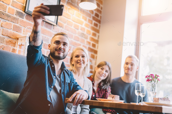Group of people taking a selfie together in a restaurant. - Stock Photo - Images