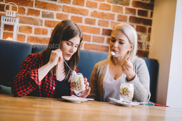 Women eating healthy dessert in a restaurant. - Stock Photo - Images