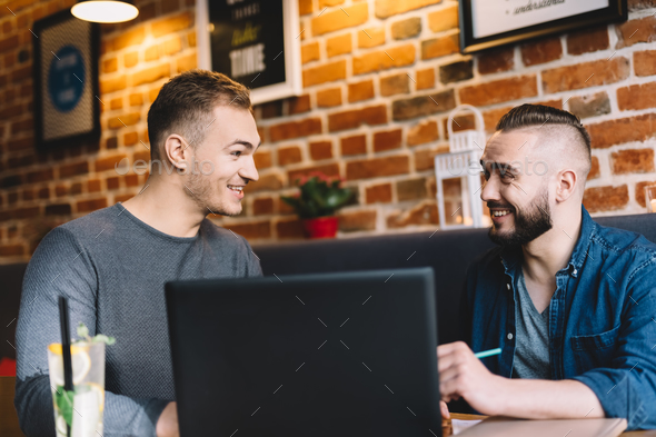 Two men in a good mood sitting by the laptop - Stock Photo - Images