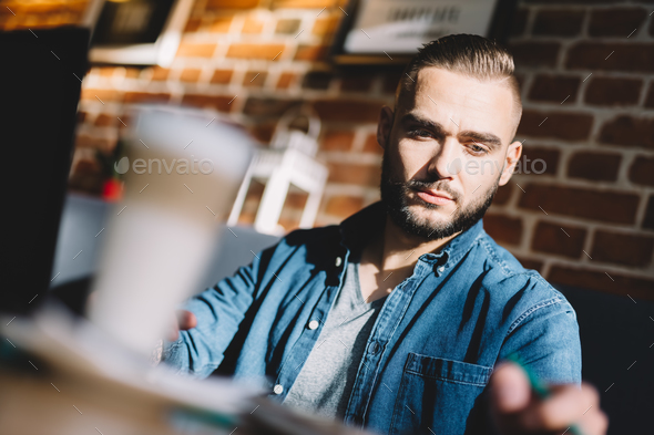 Serious young man sitting in a cafe - Stock Photo - Images