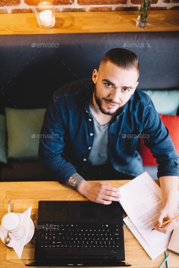 Man sitting by the table, working. - Stock Photo - Images
