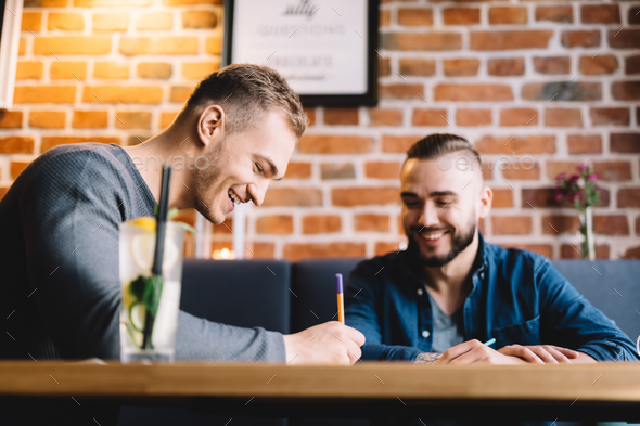 Two men sitting in a restaurant and laughing. - Stock Photo - Images