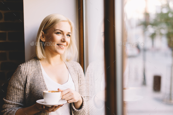 Woman with a cup of coffee standing by the window. - Stock Photo - Images