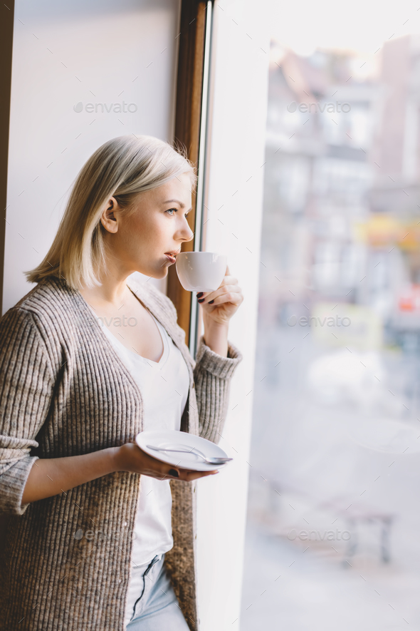 Young woman drinking coffee, looking through the window. - Stock Photo - Images