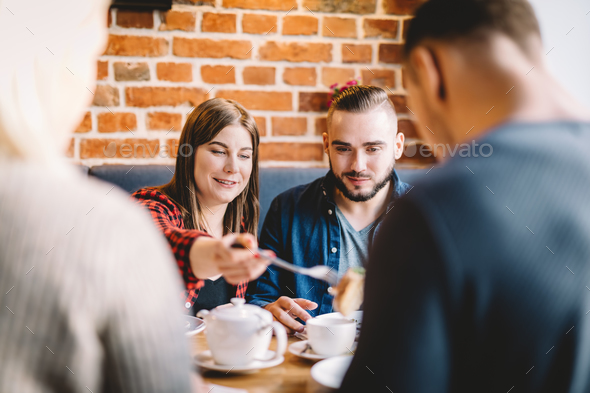 Young people eating in a restaurant. Friend's meeting. - Stock Photo - Images