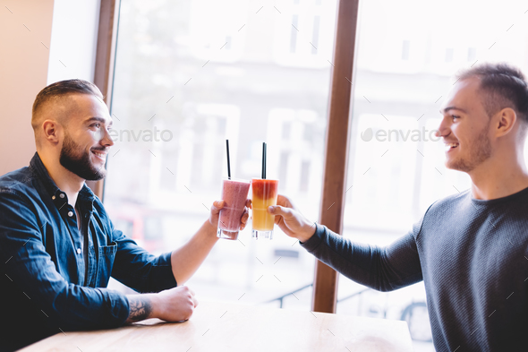 Two happy friends with colorful smoothies. - Stock Photo - Images
