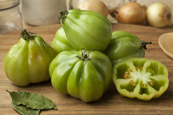 Whole and half gGreen Coeur de boeuf tomatoes - Stock Photo - Images