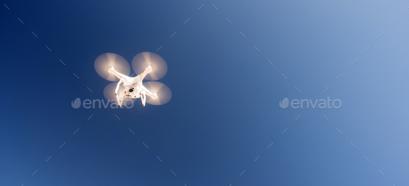 White Quadcopter Drone Flying Hoovering Blue Sky - Stock Photo - Images