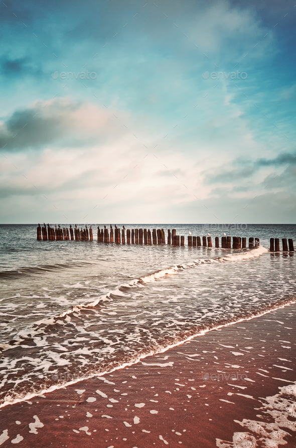 Vintage toned picture of an old wooden breakwater on a beach. - Stock Photo - Images