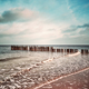 Vintage toned picture of an old wooden breakwater on a beach. - PhotoDune Item for Sale