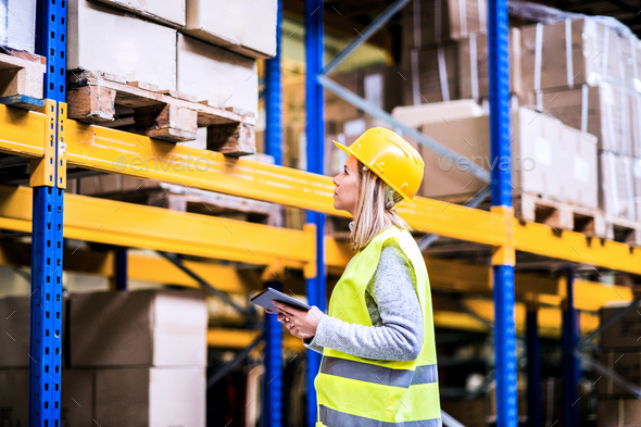 Woman warehouse worker with tablet. - Stock Photo - Images