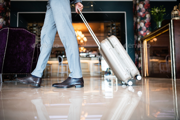 Businessman entering hotel with luggage. - Stock Photo - Images