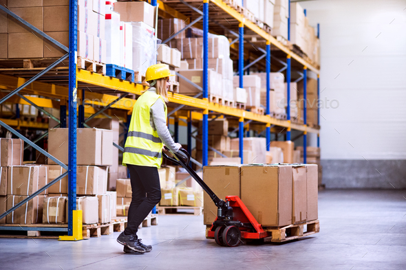 Woman warehouse worker with hand forklift truck. - Stock Photo - Images