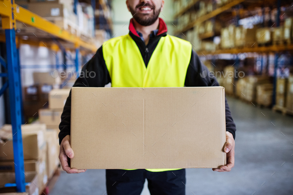 Male warehouse worker with a large box. - Stock Photo - Images