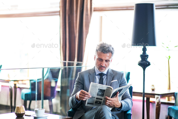 Mature businessman reading newspapers in a hotel lounge. - Stock Photo - Images