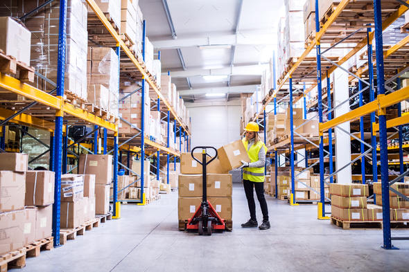 Female warehouse worker loading or unloading boxes. - Stock Photo - Images