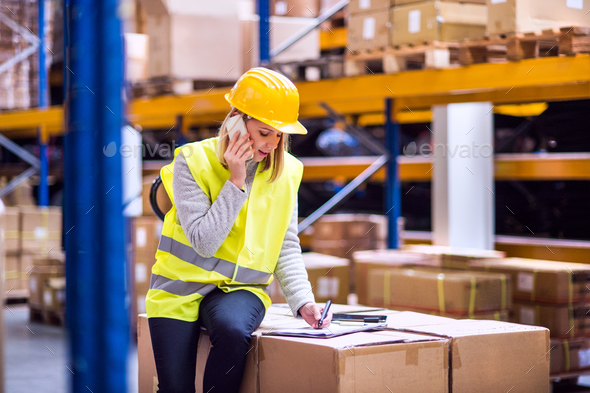 Woman warehouse worker with smartphone. - Stock Photo - Images