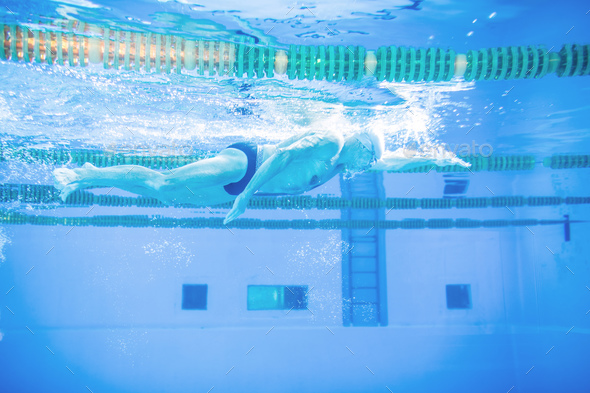 Senior man swimming in an indoor swimming pool. - Stock Photo - Images