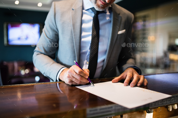 Mature businessman at hotel reception. - Stock Photo - Images