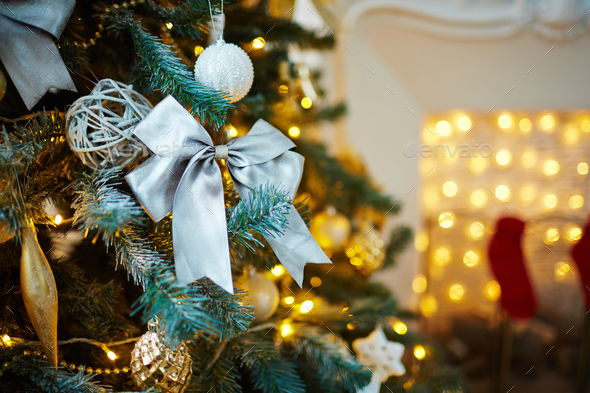 Silver bow surrounded by other decorations on xmas tree - Stock Photo - Images