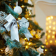 Silver bow surrounded by other decorations on xmas tree - PhotoDune Item for Sale