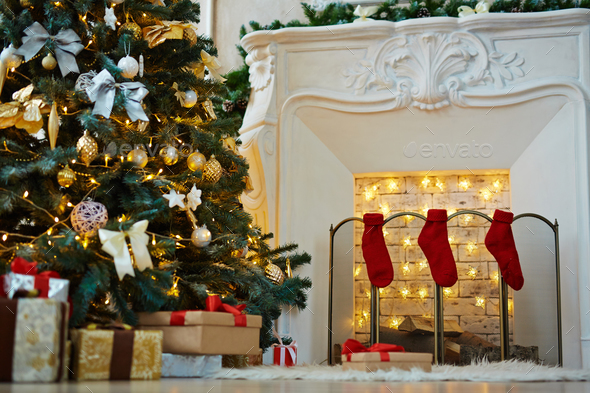 Decorated xmas tree, stack of gift-boxes and fireplace with red socks prepared for Christmas night - Stock Photo - Images
