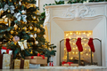 Decorated xmas tree, stack of gift-boxes and fireplace with red socks prepared for Christmas night - PhotoDune Item for Sale