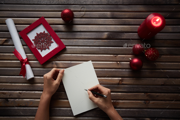 Human writing xmas wishes on blank paper sheet with holiday symbols near by - Stock Photo - Images