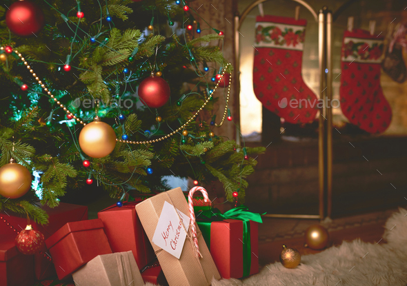 Wrapped gifts under decorated Christmas tree by fireplace - Stock Photo - Images