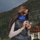 A Girl in a Blue Scarf and Wearing Sunglasses Uses a Mobile Phone. Sun Rays. - VideoHive Item for Sale