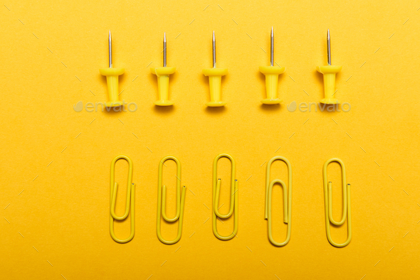 Yellow thumbtacks and clips over a yellow background - Stock Photo - Images
