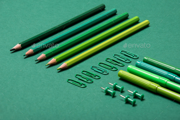 Colourful pencils, thumbtacks and clips over a green background - Stock Photo - Images