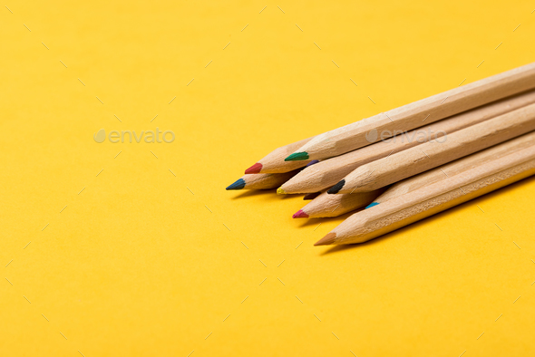 Colourful pencils over a yellow background - Stock Photo - Images