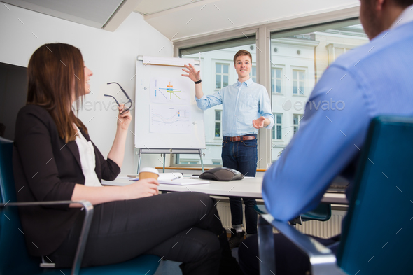 Smiling Businessman Gesturing While Giving Presentation To Colle - Stock Photo - Images
