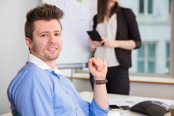 Confident Businessman Smiling While Colleague Standing At Office - Stock Photo - Images