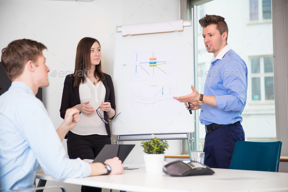Male Professional Explaining Chart To Coworkers In Office - Stock Photo - Images