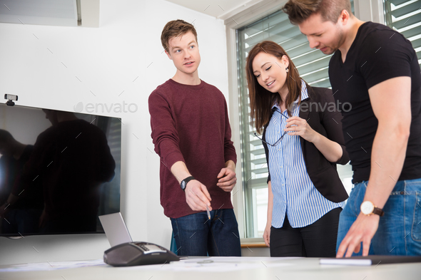 Businessman Explaining Plan To Coworkers At Desk - Stock Photo - Images