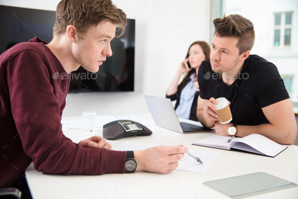 Businessmen Discussing While Colleague Using Smart Phone - Stock Photo - Images