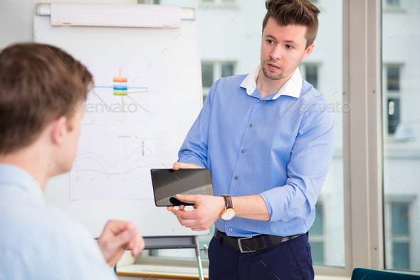 Businessman Showing Digital Tablet To Male Colleague - Stock Photo - Images