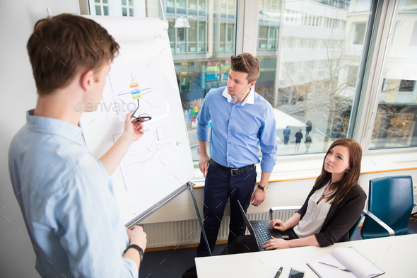 Businessman Giving Presentation To Female And Male Colleagues - Stock Photo - Images